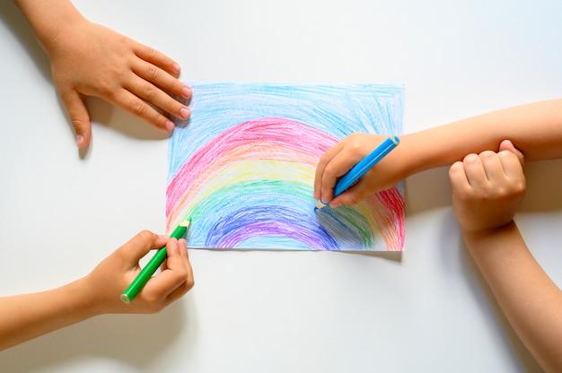 De handen van het kind trekken samen een regenboogkleurpotloden op wit