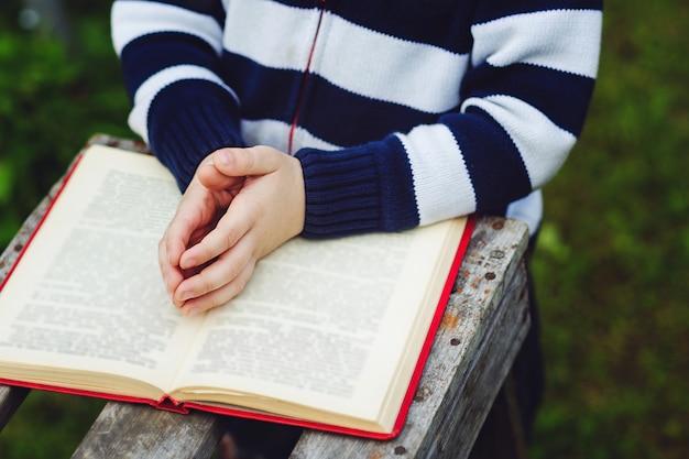De handen van het kind zijn gevouwen in gebed op een heilige bijbel.
