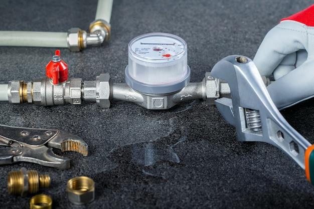 De handen van het loodgieterswerk van de loodgieterreparatie met lekken, sluiten omhoog mening. sanitair repareren.