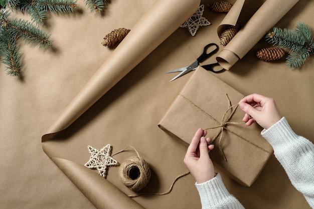 De handen van het meisje binden een strik van touw aan een geschenk verpakt in knutselpapier. kerstcadeaupapier.