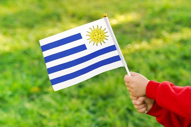 De handen van het meisje houden de vlag van uruguay