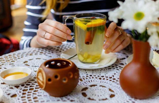De handen van het meisje houden een transparante kop thee met kaneel, munt, sinaasappel op de lijst met honing.