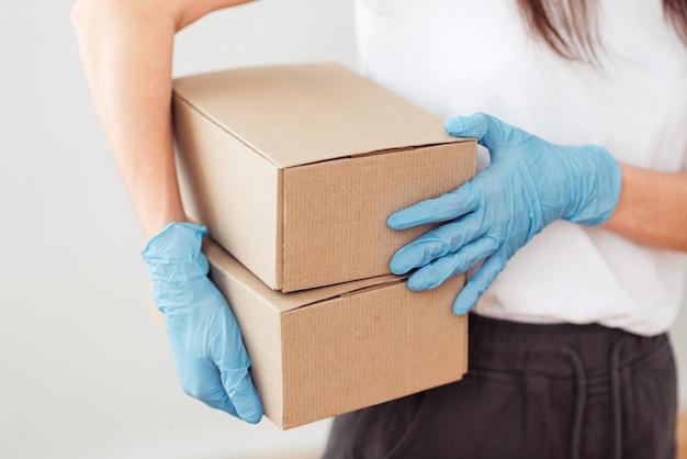 De handen van het meisje in handschoenen houden twee kleine dozen vast, verzenden en verpakken van het pakket, veilige levering