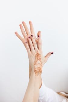 De handen van het meisje op wit met hennapatroon