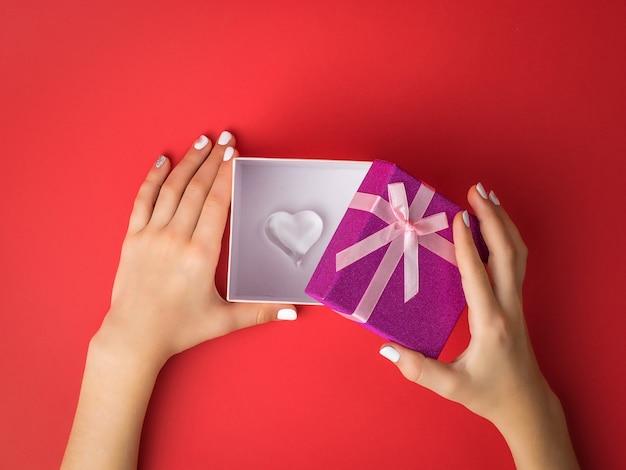 De handen van het meisje openen een geschenkdoos met daarin een glazen hart. verrassing in de handen van een meisje.