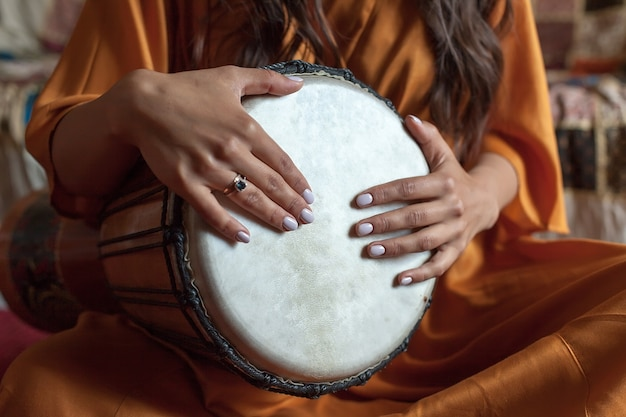 De handen van het meisje spelen een prachtige melodie op een afrikaanse trommel. meditatie.