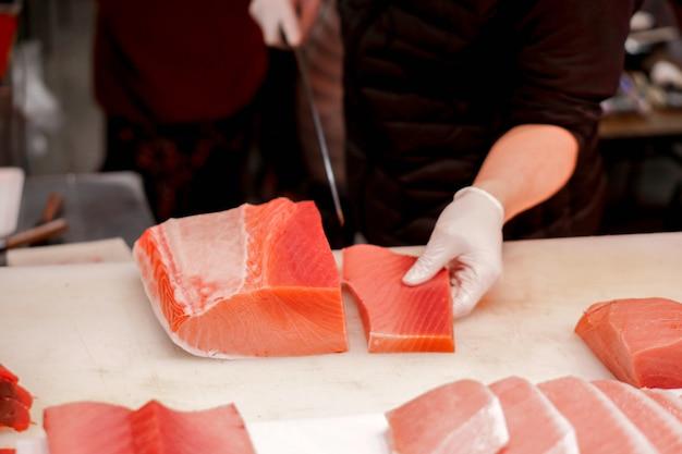 De handen van japanse chef-kok die chef-kokmes gesneden stuk verse tonijnvis gebruiken voor verkopen aan klant in de markt van ochtendvissen, japan.