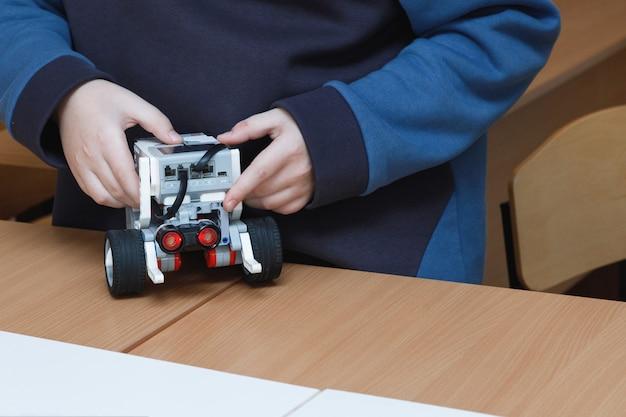 De handen van kinderen besturen speelgoedrobots