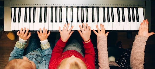 De handen van kinderen die de elektrische piano spelen. muziekinstrument in handen van kinderen