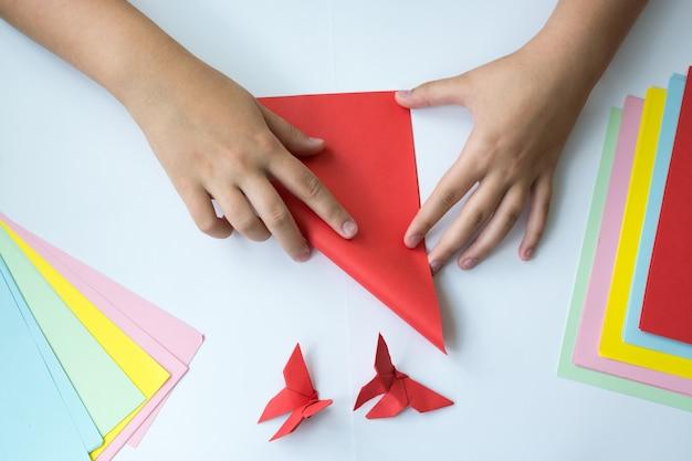 De handen van kinderen doen origami een vlinder. kleur papier ligt op een tafel.