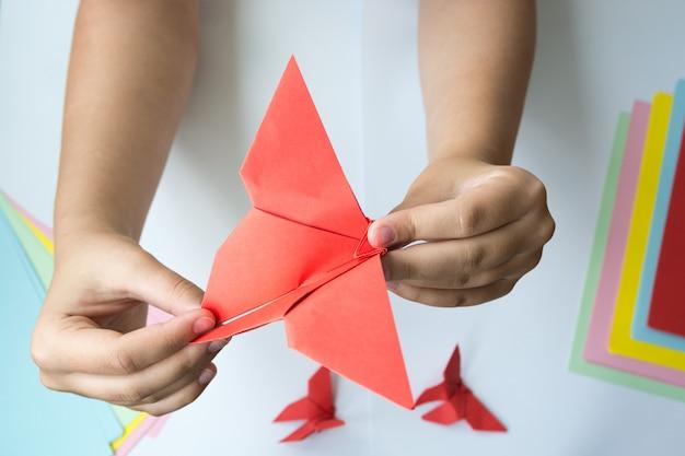 De handen van kinderen doen origami een vlinder.