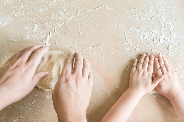 De handen van kinderen en papa's maken rauw deeg