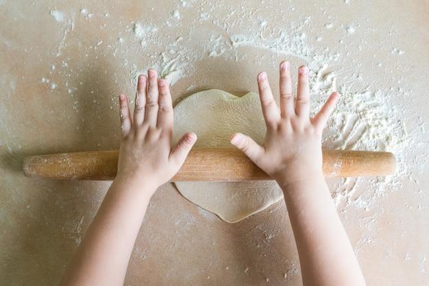 De handen van kinderen gerold deeg