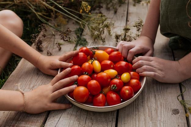De handen van kinderen grijpen naar een bord met rode tomaten die op een houten tafel staan.
