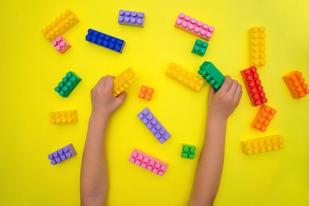 De handen van kinderen houden de details van de constructeur op een gele achtergrond.