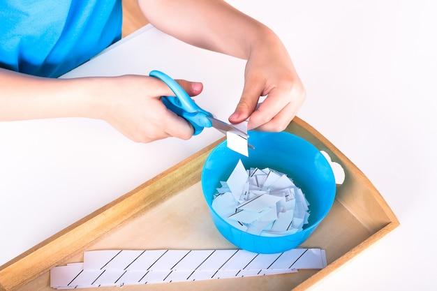 De handen van kinderen houden een blauwe schaar vast en snijden het papier.
