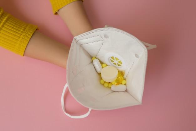 De handen van kinderen houden een gasmasker met vitamines vast.