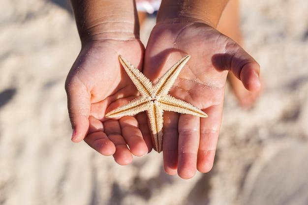 De handen van kinderen houden een mooie zeester op het zandstrand.