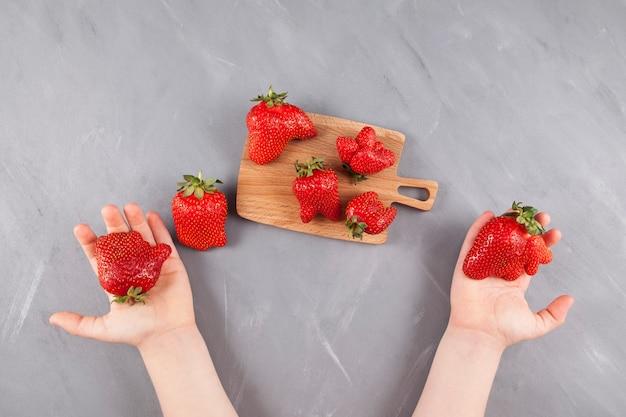 De handen van kinderen houden grappig gevormde biologische aardbeien vast. houten serveerplank met heldere lelijke bessen.