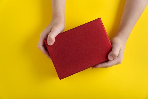 De handen van kinderen houden rode kartonnen doos op gele achtergrond. bovenaanzicht.