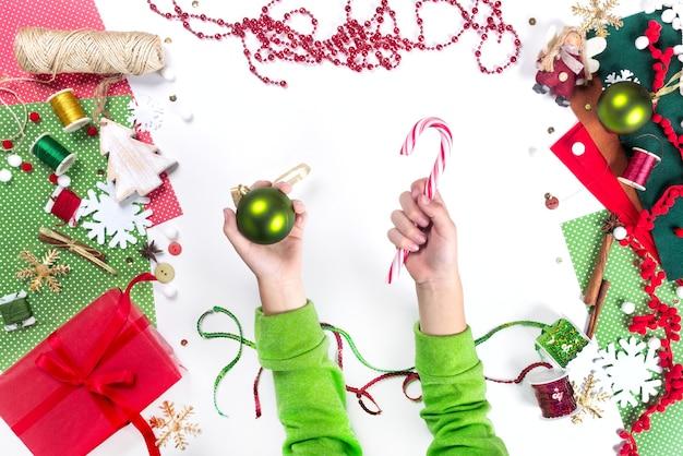 De handen van kinderen houden snoep en kerstbal vast. decoratie presenteert het maken van plat lag bovenaanzicht xmas viering voorbereiding diy concept decor op witte achtergrond.