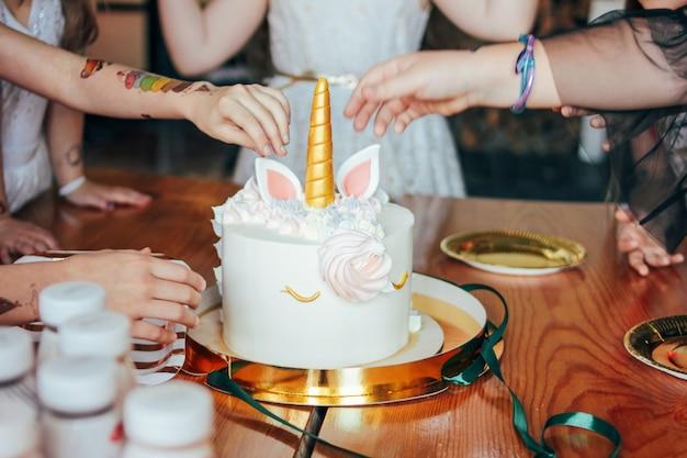 De handen van kinderen kleine meisjes reiken naar de cake. grote mooie cake eenhoorn op de verjaardag van kleine prinses op feestelijke tafel