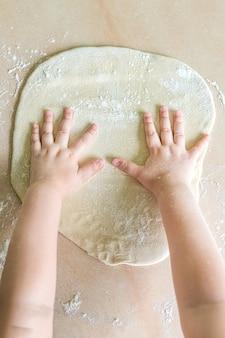 De handen van kinderen maken deeg