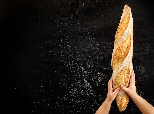 De handen van kinderen met een stokbrood op een zwarte achtergrond.