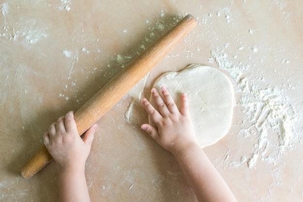 De handen van kinderen rolden deeg