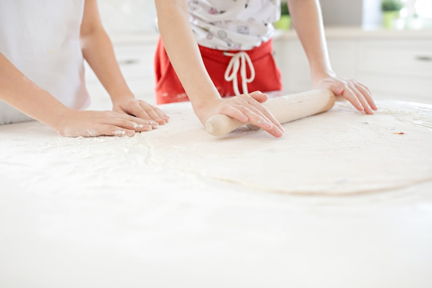 De handen van kinderen rollen het pizzadeeg op een witte lijst uit. samen plezier maken in de keuken. uitzicht van boven.