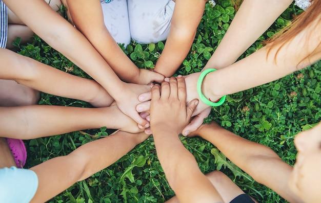 De handen van kinderen samen op een achtergrond van gras.