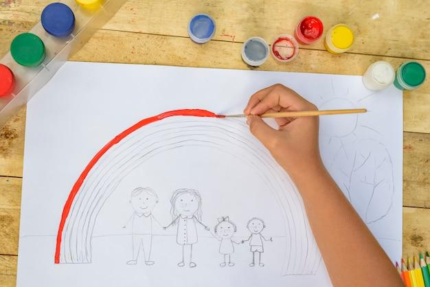 De handen van kinderen schilderen een tekening met een penseel en verf. bovenaanzicht