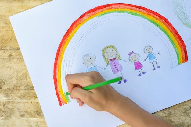 De handen van kinderen schilderen een tekening met een penseel en verf