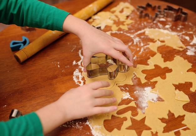 De handen van kinderen sluiten omhoog uit deegvormen voor peperkoek