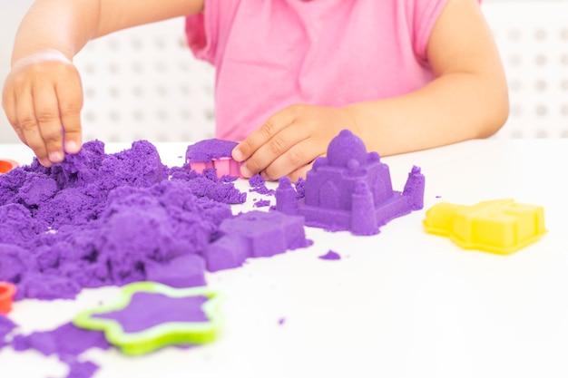 De handen van kinderen spelen kinetisch zand in quarantaine. paars zand op een witte tafel. coronapandemie