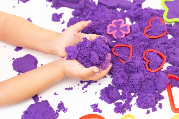 De handen van kinderen spelen kinetisch zand