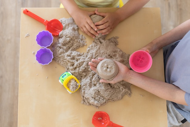 De handen van kinderen spelen met kinetisch zand en speelgoed op de tafel
