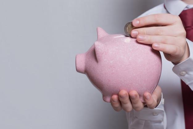 De handen van kinderen stoppen een munt in een roze spaarvarken. bedrijfsconcept. detailopname
