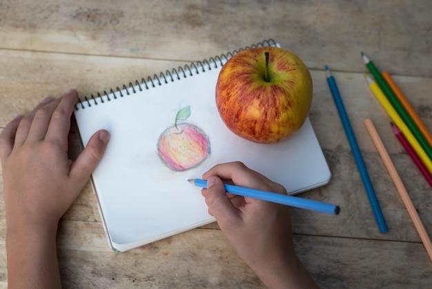 De handen van kinderen tekenen een appel met kleurpotloden. bovenaanzicht