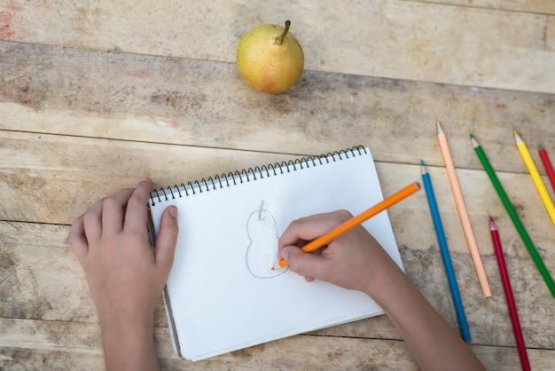 De handen van kinderen tekenen een peer met kleurpotloden. bovenaanzicht