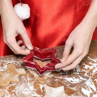 De handen van kinderen uitgesneden kerstkoekjes met deegvormen.