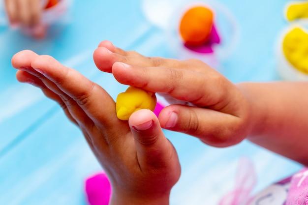 De handen van kinderen vormen kleurrijk deegclose-up. jeugd kinderen baby's onderwijs concept