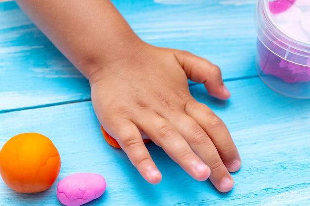 De handen van kinderen vormen kleurrijk deegclose-up. jeugd kinderschoenen kinderen baby's onderwijs concept