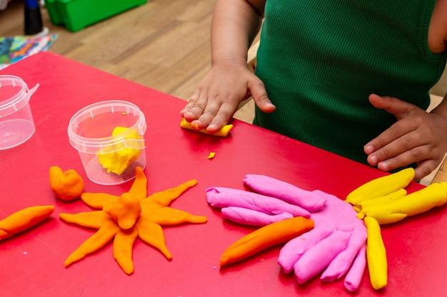De handen van kinderen vormen kleurrijk deegclose-up.