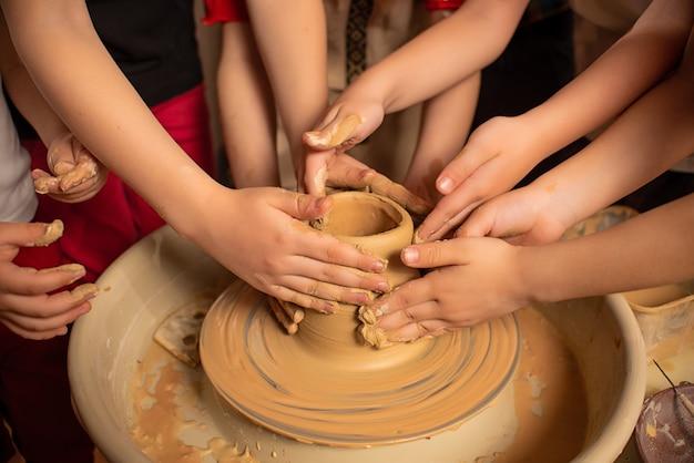 De handen van kinderen werken met klei op een speciale machine