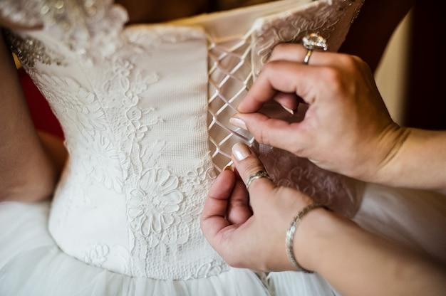 De handen van mama binden het korset van de bruidsjurk van de bruid