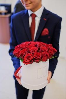 De handen van mannen houden een emmer rode rozen in een emmer