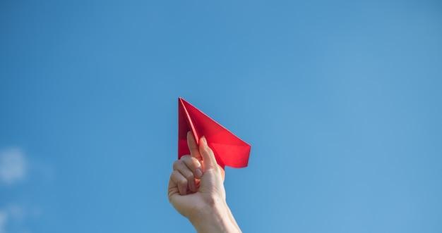 De handen van mannen houden een rode papieren raket met een helderblauwe achtergrond.