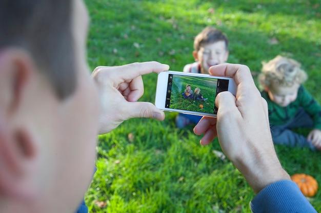 De handen van mannen houden een smartphone en maken foto van gelukkige kinderen. vader neemt foto's van zijn kinderen aan de telefoon in de natuur. detailopname