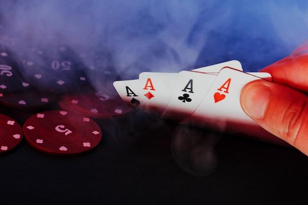 De handen van mannen houden kaarten tegen de achtergrond van het spelen van chips